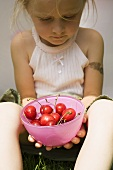 Seated girl holding bowl of fresh red cherries