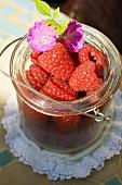 Fresh raspberries and purple flowers in preserving jar