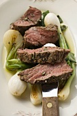 Beef steak, sliced, with roasted spring onions