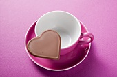 Chocolate heart on pink coffee cup