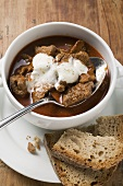 Goulash soup with sour cream in soup cup, slices of bread