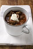 Goulash soup with sour cream in cup