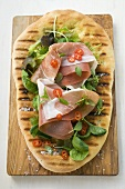 Parma ham, herbs and chili rings on pizza bread