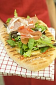 Woman holding pizza bread topped with Parma ham, herbs, chilli rings
