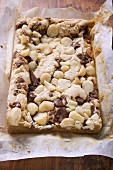 Chocolate slice with macadamia nuts in baking parchment