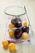 Plums, mirabelles, sugar, jam jar and spoon