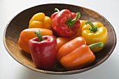 Yellow, orange and red peppers in wooden bowl