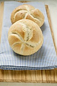 Two bread rolls on blue and white checked cloth