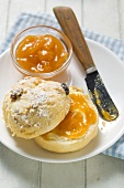Raisin scone with apricot jam on plate