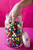 Hand reaching into jar of coloured bubble gum balls