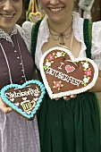 Two women in national dress with Lebkuchen hearts at Oktoberfest