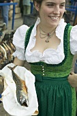 Woman holding Steckerlfisch (skewered fish) at Oktoberfest