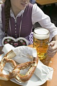 Woman with litre of beer and pretzel at Oktoberfest