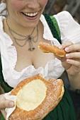 Frau isst Auszogene (süsses Schmalzgebäck) beim Oktoberfest