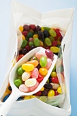 Coloured jelly beans in plastic bag with scoop