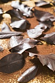 Several different chocolate leaves on cocoa powder