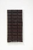 A bar of dark chocolate in cellophane