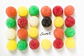 Many coloured jelly sweets in rows with the word 'Sweet'