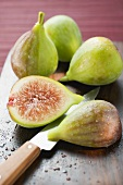 Three whole figs and two fig halves with knife
