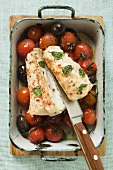Monkfish with cherry tomatoes and olives in roasting tin