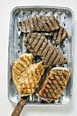 Grilled meat in aluminium grill tray (overhead view)