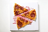 Three slices of pepperoni pizza on pizza box