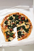 Spinach, tomato and cheese pizza in pizza box