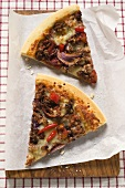 Two slices of mince and onion pizza on paper