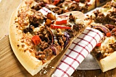 Mince and onion pizza, partly sliced