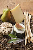 Cheese still life with pears, fig & grissini on wicker plate