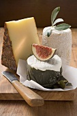 Cheese still life with fig on chopping board