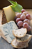 Pieces of Appenzeller and blue cheese, red grapes, bread