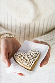 Hands holding gingerbread heart on napkin (Christmassy)