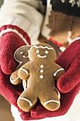 Hands in woollen gloves holding gingerbread men