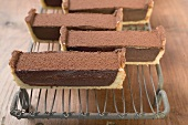 Rectangular chocolate tart with cocoa powder (in pieces)