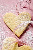 Pastry hearts with icing sugar and pink ribbon