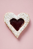Heart-shaped biscuit with raspberry jam and icing sugar