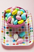 Coloured sugared almonds in pink bowl on tray