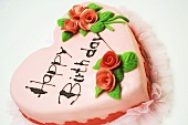 Pink heart-shaped birthday cake with marzipan roses