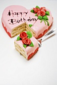 Pink heart-shaped birthday cake with piece on server
