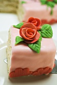 Piece of birthday cake with marzipan roses on cake server