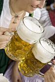 Women clinking litres of beer together (Oktoberfest, Munich)