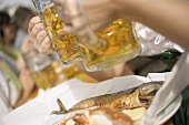 Hands clinking two litres of beer together (Oktoberfest, Munich)