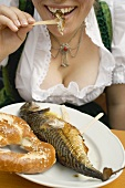 Woman eating Steckerlfisch & pretzel (Oktoberfest, Munich)