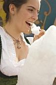 Woman eating candyfloss (Oktoberfest, Munich)