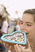 Woman biting into Lebkuchen heart (Oktoberfest, Munich)