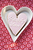 Heart-shaped biscuit with the word Love in white dish