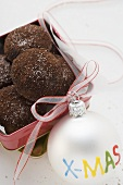 Chocolate kisses in biscuit tin, Christmas bauble beside it