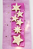 Star biscuits with sugar on purple paper (for Christmas)