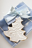 Gingerbread fir tree with white icing beside gift